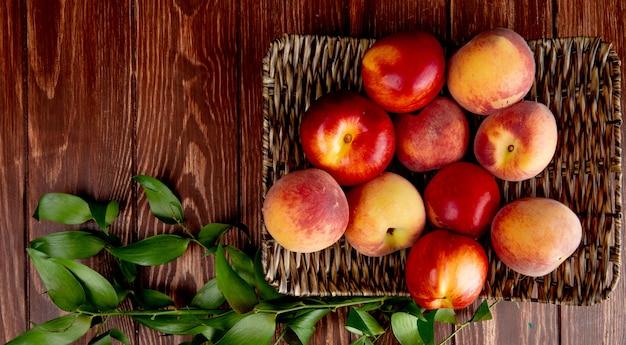 Взгляд сверху персиков в плите корзины на деревянной поверхности украшенной листьями