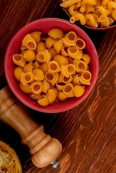 Вид сверху макаронных изделий с другими видами макарон в мисках и солью на деревянной поверхности