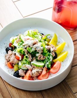 Салат из тунца с оливками, помидорами и листьями салата