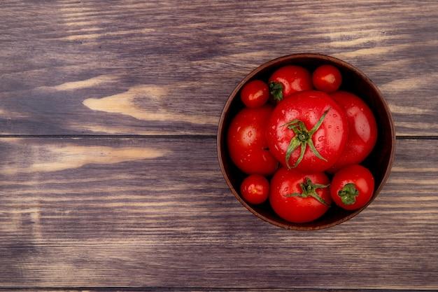 Вид сверху помидоры в миску на правой стороне и деревянной поверхности с копией пространства