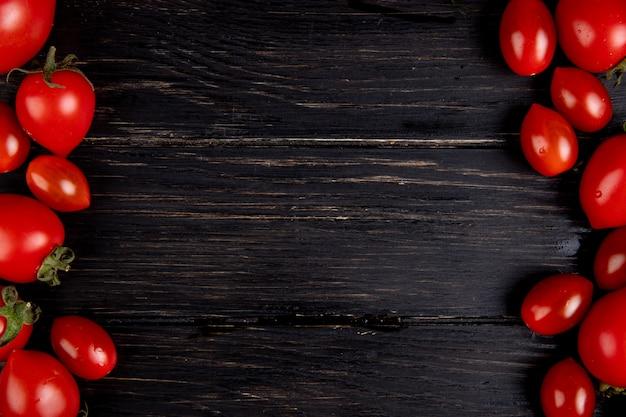 左側と右側のトマトとコピースペースを持つ木製の表面のトップビュー