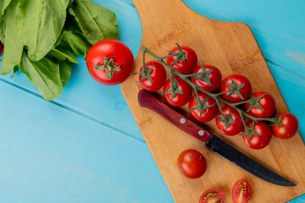 まな板の上のナイフと青い表面にほうれん草のトマトのトップビュー