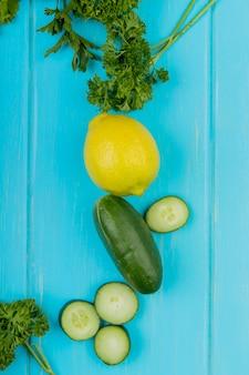 青い表面にレモンとキュウリのコリアンダーとして野菜のトップビュー