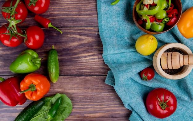 木製の表面に青い布とキュウリのトマトピーマンのままにニンニククラッシャーとレモンのペッパートマトとして野菜のトップビュー