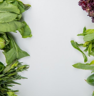 Взгляд сверху овощей как огурец базилика мяты шпината на белой поверхности с космосом экземпляра