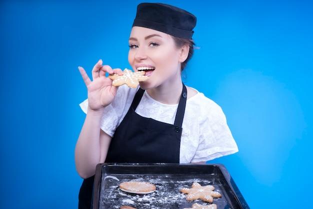 焼きたてのジンジャーブレッドのクッキーを試飲する魅力的な主婦