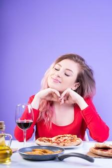目を閉じてテーブルに座って魅力的な女性
