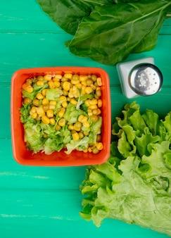 緑の表面にスライスしたレタスとほうれん草の塩全体のレタスと黄色のエンドウ豆のボウルのトップビュー