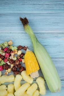 木製の表面にカットトウモロコシと調理トウモロコシのスキットルズポップコーンとコーンポップシリアルのトップビュー