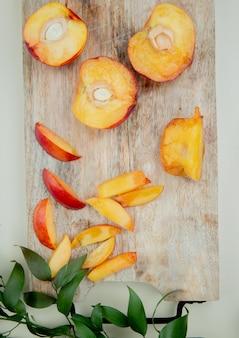 葉で飾られた白い表面にまな板の上のカットとスライスされた桃のトップビュー