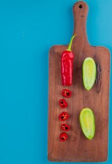 コピースペースを持つまな板と青い表面に唐辛子とキュウリとしてカットとスライスした野菜のトップビュー