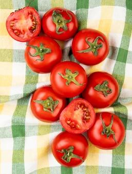 Вид сверху нарезанные и целые помидоры на поверхности плед ткани