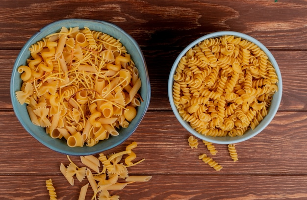 Взгляд сверху различных видов макаронных изделий и макарон ротини в мисках и на деревянной поверхности