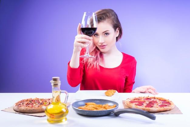 Милая женщина, поднимая бокал красного вина