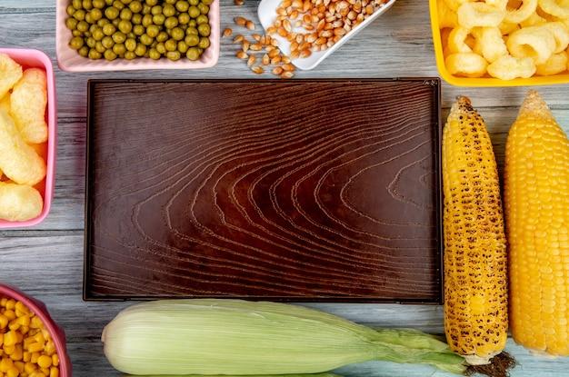木製の表面にグリーンピースのトウモロコシ種子コーンポップシリアルとトウモロコシの穂軸と空のトレイのトップビュー