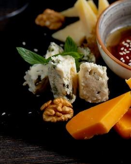 Различные виды сыра с грецкими орехами и соусом