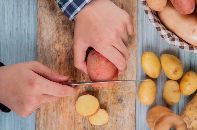 バスケットと木製の表面に他のものとまな板の上のナイフでジャガイモを切る手のトップビュー