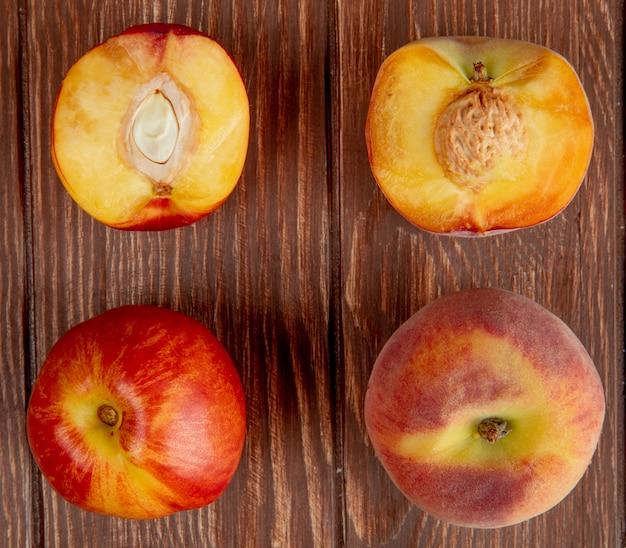 Вид сверху рисунка из целых и полусрезанных персиков на деревянной поверхности