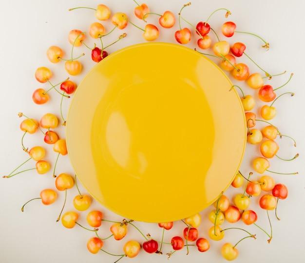Вид сверху красной и желтой вишни с пустой желтой табличкой в центре на белой поверхности