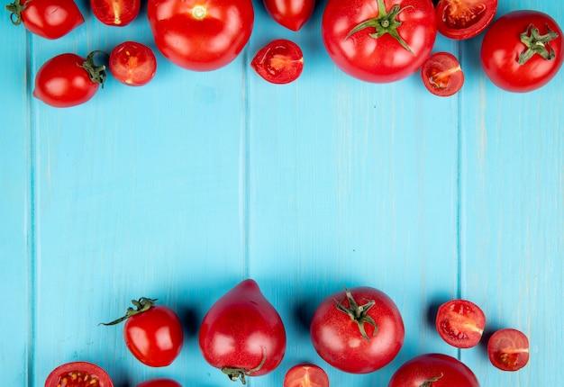 コピースペースを持つ青い表面上の全体とカットトマトのトップビュー