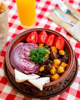 Жареное мясо с картофелем, подается с луком, помидорами и зеленью