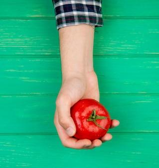 緑の表面にトマトを持つ女性の手の上から見る
