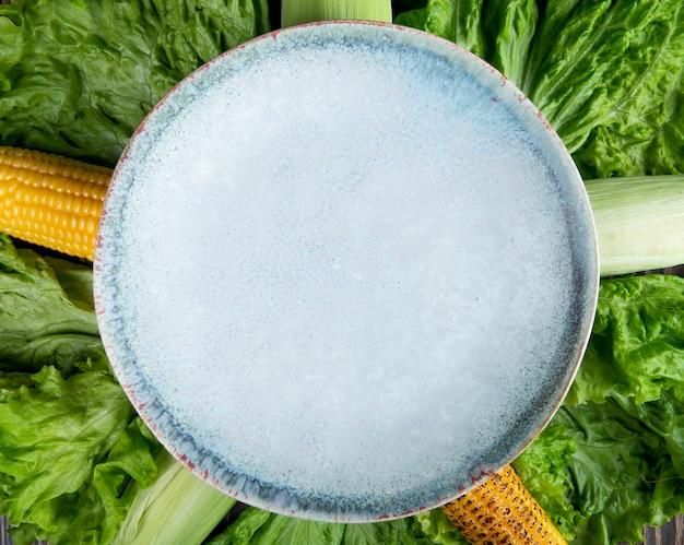トウモロコシとレタスの背景を持つ空のプレートのクローズアップビュー