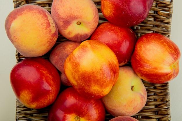 Взгляд конца-вверх персиков в плите корзины на белой таблице