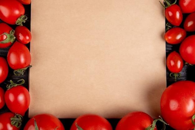 Взгляд конца-вверх томатов вокруг блокнота на деревянном столе с космосом экземпляра