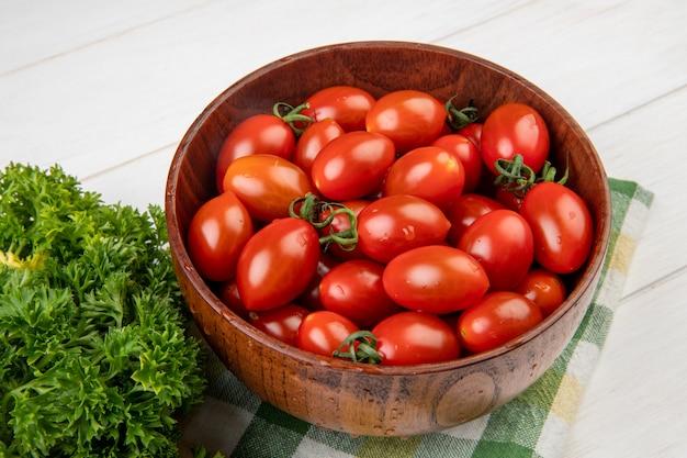 Взгляд конца-вверх томатов в шаре с китайским кориандром на ткани на деревянном столе
