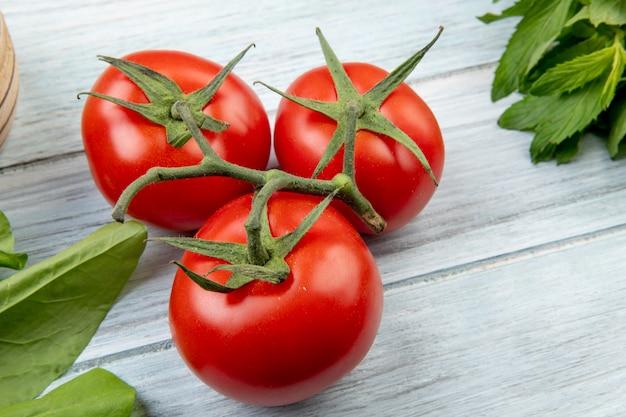 木製のテーブルにトマトとほうれん草と緑のミントの葉のクローズアップビュー