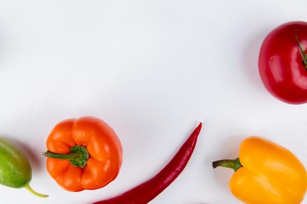 コピースペースを持つ白いテーブルに唐辛子きゅうりとして野菜のクローズアップビュー