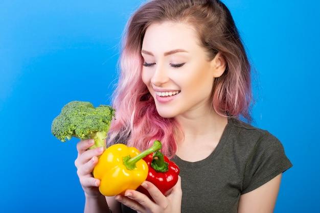 新鮮なブロッコリーの赤と黄色のコショウを見て健康な女性