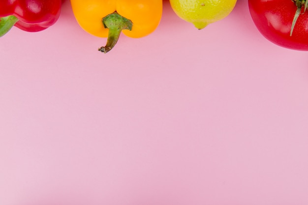 コピースペースと紫色の背景にレモンとペッパートマトとして野菜のクローズアップビュー