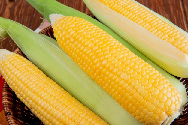 調理済みおよび未調理のトウモロコシがいっぱい入ったかごのクローズアップビュー