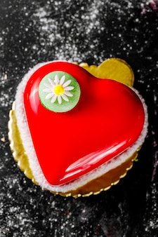 カモミールで飾られた赤いトッピングでハート型のケーキ