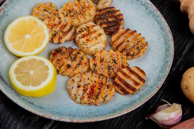 Крупным планом вид жареных ломтиками картофеля и ломтиками лимона в тарелку с чесноком на деревянной поверхности