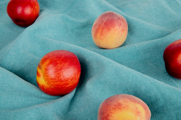 Взгляд конца-вверх картины персиков на голубой ткани