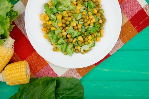 黄色のエンドウ豆とコーンほうれん草のレタスとスライスしたレタスのプレートの布と緑のテーブルのクローズアップビュー