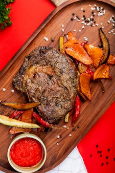 Жареный мясной стейк с овощами и семечками