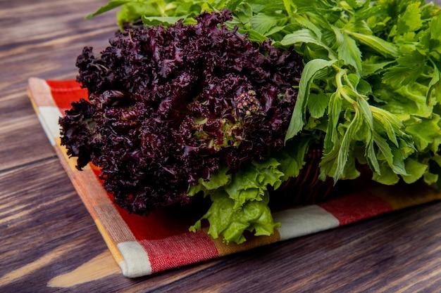 木製のテーブルの布の上のバスケットにコリアンダーミントレタスバジルとして緑の野菜の側面図
