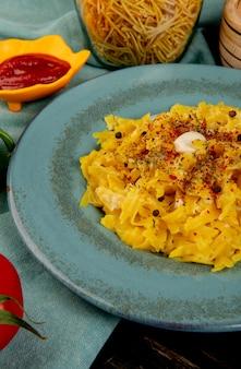 青い布と木製のテーブルの上のケチャップスパゲッティトマトとプレートのマカロニパスタの側面図