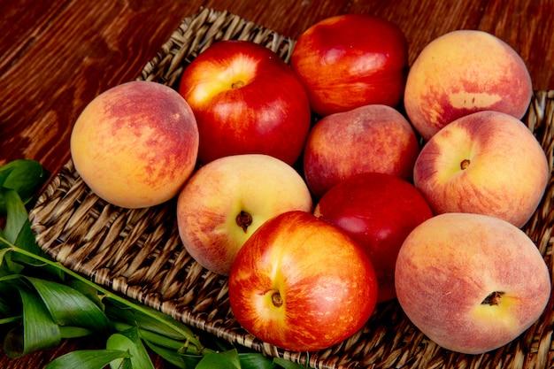 Вид сбоку персики в корзине на деревянный стол украшен листьями