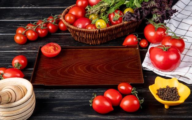 トマトグリーンミントとして野菜の側面図はバスケットにバジルを残し、木製のテーブルにトレイ黒胡椒ニンニククラッシャーでトマトをカット
