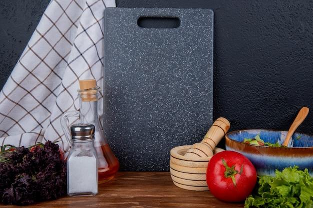 木製の表面と黒の背景にバジル塩溶かしバタートマトガーリッククラッシャーレタスとまな板と布と野菜のサラダの側面図