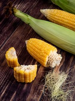 木製のテーブルにトウモロコシシルクとカットと全体のトウモロコシの側面図