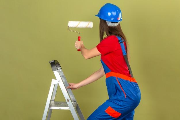 緑の背景にペイントローラーを保持している梯子の上の建設の制服と青い安全ヘルメットの若い女性