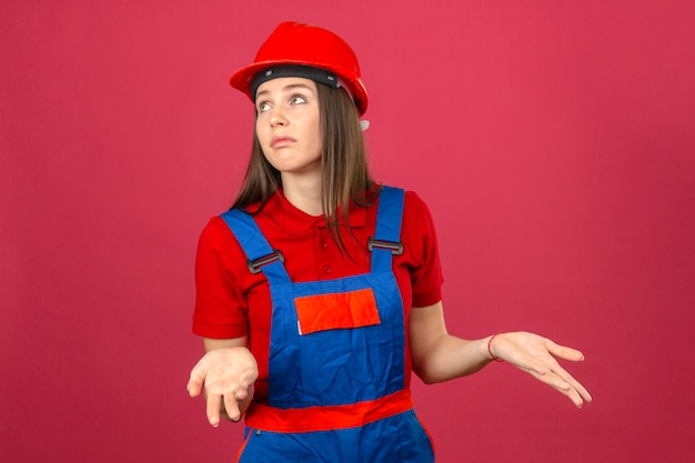 建設の制服と赤の安全ヘルメット無知で混乱している若い女性腕と手で混乱した表現は、濃いピンクの背景の上に立って発生