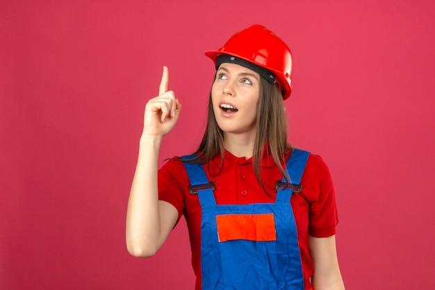 暗いピンクの背景に指を上向きに素晴らしいアイデアを持つ建設の制服と赤い安全ヘルメットの若い女性