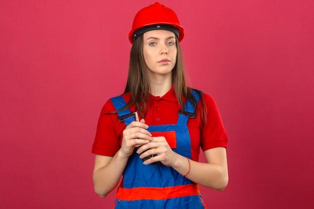 濃いピンクの背景に手でテープラインを保持している深刻な顔をしてカメラを見て建設の制服と赤い安全ヘルメットの若い女性